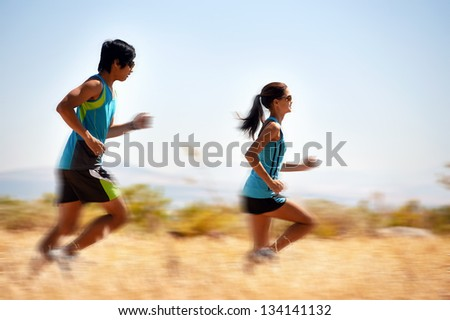 action motion blur of running athlete in field with fitness - stock photo