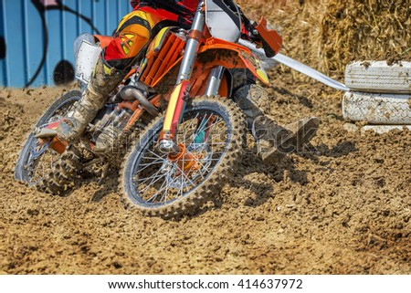 Action packed scene of a moto cross rider in a race, who plows through deep mud. - stock photo