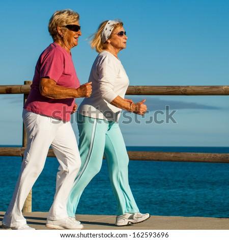 Action portrait of golden age women having early morning jog. - stock photo