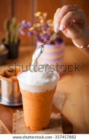 Action scene of adding cold milk foam on Iced Thai milk tea in plastic glass on wood table in cafe - stock photo