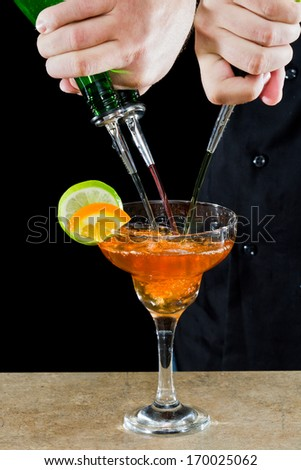action shot of a bartender pouring red margarita using multiple bottles - stock photo