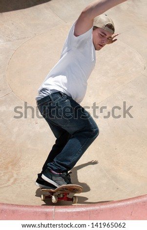 Action shot of a skateboarder skating in a concrete skateboarding bowl at the skate park. - stock photo