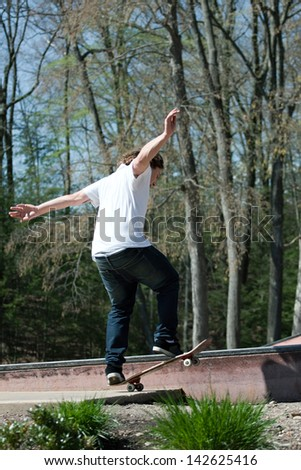 Action shot of a skateboarder skating on a rail at the skate park.