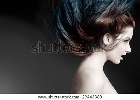 Action shot of an attractive model swinging her hair. - stock photo