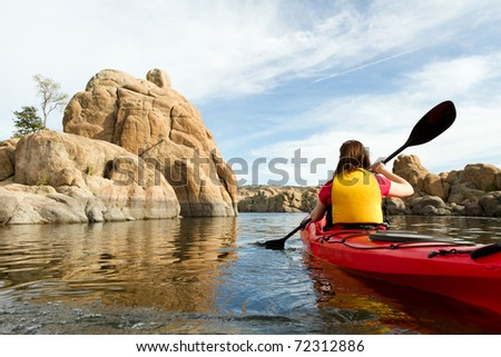 Action Shot of Woman Paddling Kayak in Lake - stock photo