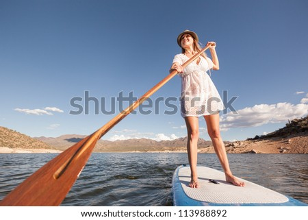 Action Shot of Young Woman on Paddle Board - stock photo