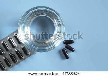Activated charcoal capsules and glass of water on a blue background, top view
