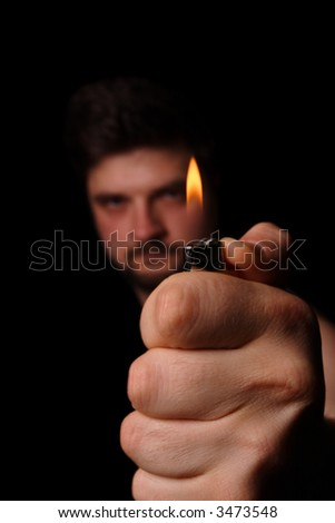 activated lighter with flame in hand pressured with thumb