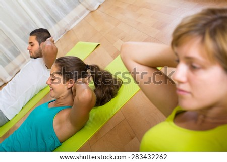 Active adult sportsmen at group training in fitness club. Focus on girl - stock photo
