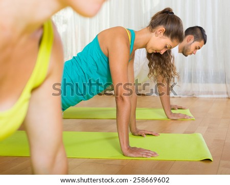 Active adults at group training in fitness club. Focus on girl  - stock photo