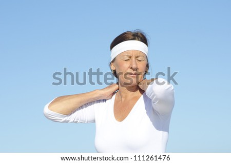 Active and attractive looking senior woman relaxed and concentrated with hands on neck, feeling pain, isolated with blue sky as background and copy space. - stock photo