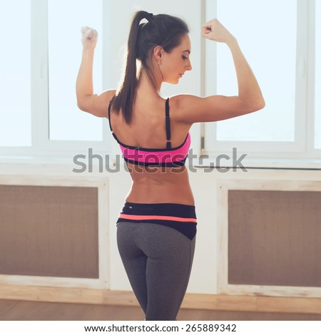 Active athletic sporty woman in sport outfit standing showing biceps muscles of the back and buttocks rear view healthy lifestyle. - stock photo