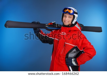Active attractive guy walking with ski in hands. Looking and smiling at camera isolated over blue background  - stock photo