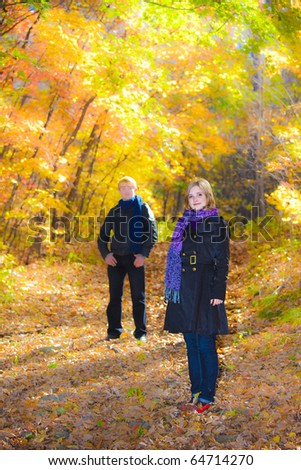 Active beautiful boy and girl in autumn wood