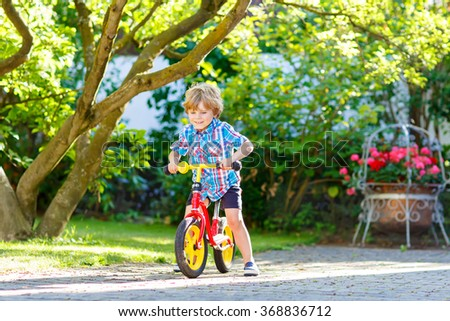 Active blond kid boy in colorful clothes driving bicycle in domestic garden. Toddler child dreaming and having fun on warm summer day. outdoors games for children - stock photo