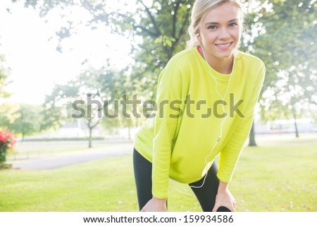 Active cheerful blonde pausing after a run in a park on a sunny day - stock photo