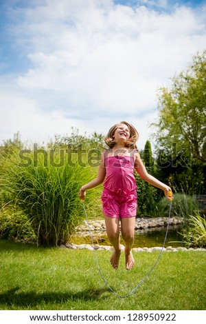 Active child - happy girl jumping with skipping rope outdoor, copy space - stock photo