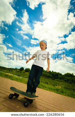 Active childhood. Little man skateboarding. Skater boy child kid with his skateboard. Outdoor.