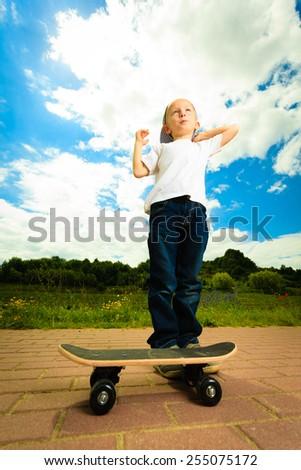 Active childhood. Little man skateboarding. Skater boy child kid with his skateboard. Outdoor. - stock photo
