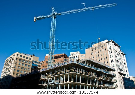 active construction site and crane over a new city building taking shape with a beautiful deep blue sky in the background - stock photo