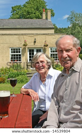 Active Couple in their Eighties enjoy a drink on a Summers Day - stock photo