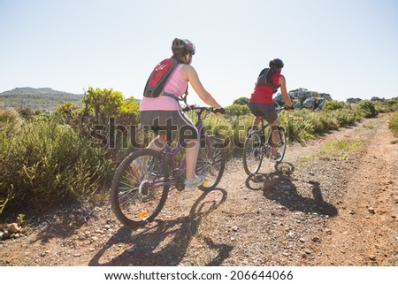 Active couple on a bike ride in the countryside on a sunny day - stock photo