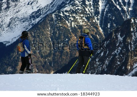 Active couple on a snowy mountain.