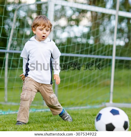 Active cute little kid boy playing soccer and football and having fun, outdoors on field. Active leisure with children on warm sunny summer day.