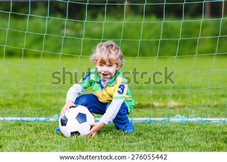Active cute little toddler playing soccer and football and having fun, outdoors on field. Active leisure with children on warm sunny summer day. - stock photo
