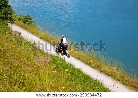 Active dad running, pushing a stroller and listening to music - stock photo