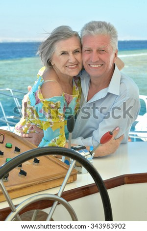 Active elderly couple smiling resting on the sea - stock photo