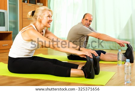Active elderly couple training on mats  indoor - stock photo