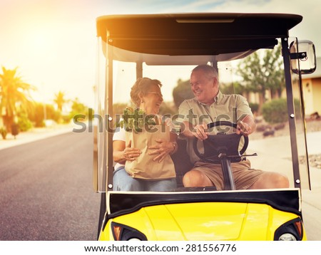 active elderly senior couple getting groceries on golf cart with orange lens flare and warm filter over image. Shot with selective focus. - stock photo