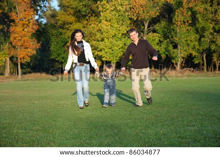 Active Family Enjoying Walk In autumn Park - stock photo