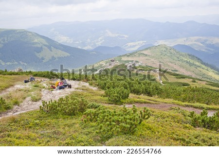 Active family hikers and their pet dog sitting on a remote mountainside - stock photo