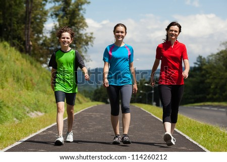 Active family - mother and kids walking , running outdoor - stock photo