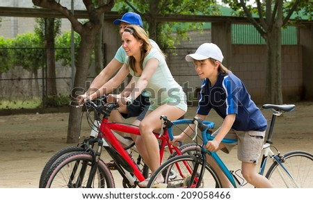 Active family of three in the summer on the street riding bikes - stock photo
