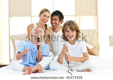 Active family singing together sitting on bed - stock photo