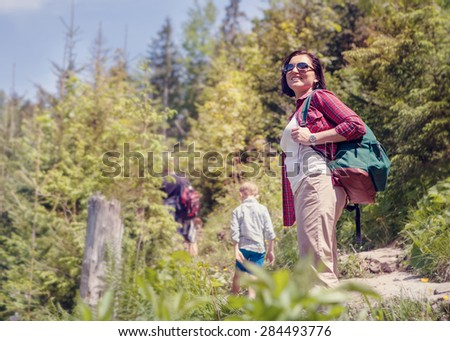 Active family walk in mountain forest - stock photo