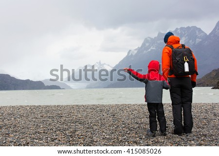 active father and his son enjoying the view of glacier grey at lago grey and having adventure hike at torres del paine national park, patagonia, chile