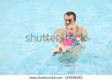 Active father teaching his toddler daughter to swim in the pool on her back - stock photo
