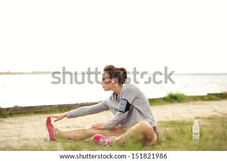 Active Female runner stretching before doing her summer fitness run - stock photo