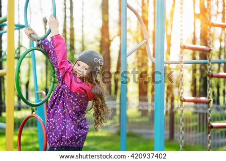Active girl doing sport exercises on a playground. Healthy lifestyle. Happy childhood concept. - stock photo