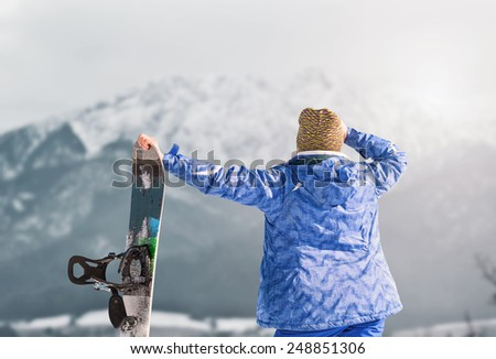 Active girl with snowboard on the snow mountain view - stock photo