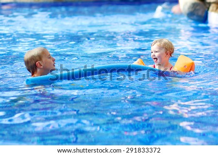 Active happy children, curly toddler girl and her brother having fun relaxing and floating on an inflatable toy in a pool on sunny day during summer vacation in resort - stock photo