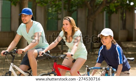 Active happy couple with teenager son cycling through city in summer day - stock photo