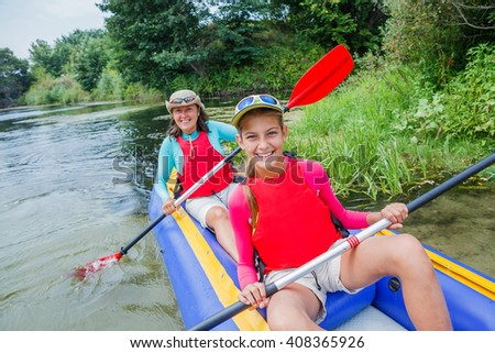 Active happy family. Girl with her mother having fun together enjoying adventurous experience kayaking on the river on a sunny day during summer vacation - stock photo