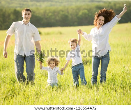 Active happy family jumping outdoors in spring green field - stock photo