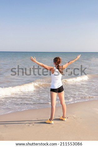 Active happy sportswoman with raised up hands. Caucasian girl is enjoying sea after exercising at the beach. Female athlete after work out in sunny light. Weight loss. Healthy lifestyle. Copy space.