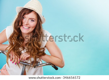 Active happy woman riding bike bicycle. Young girl in hat, white shirt and shorts. Healthy lifestyle and recreation leisure activity. Studio shot.